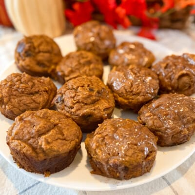 pumpkin sourdough muffins chocolate chip and cinnamon glace on a plate with fall decorations in the background
